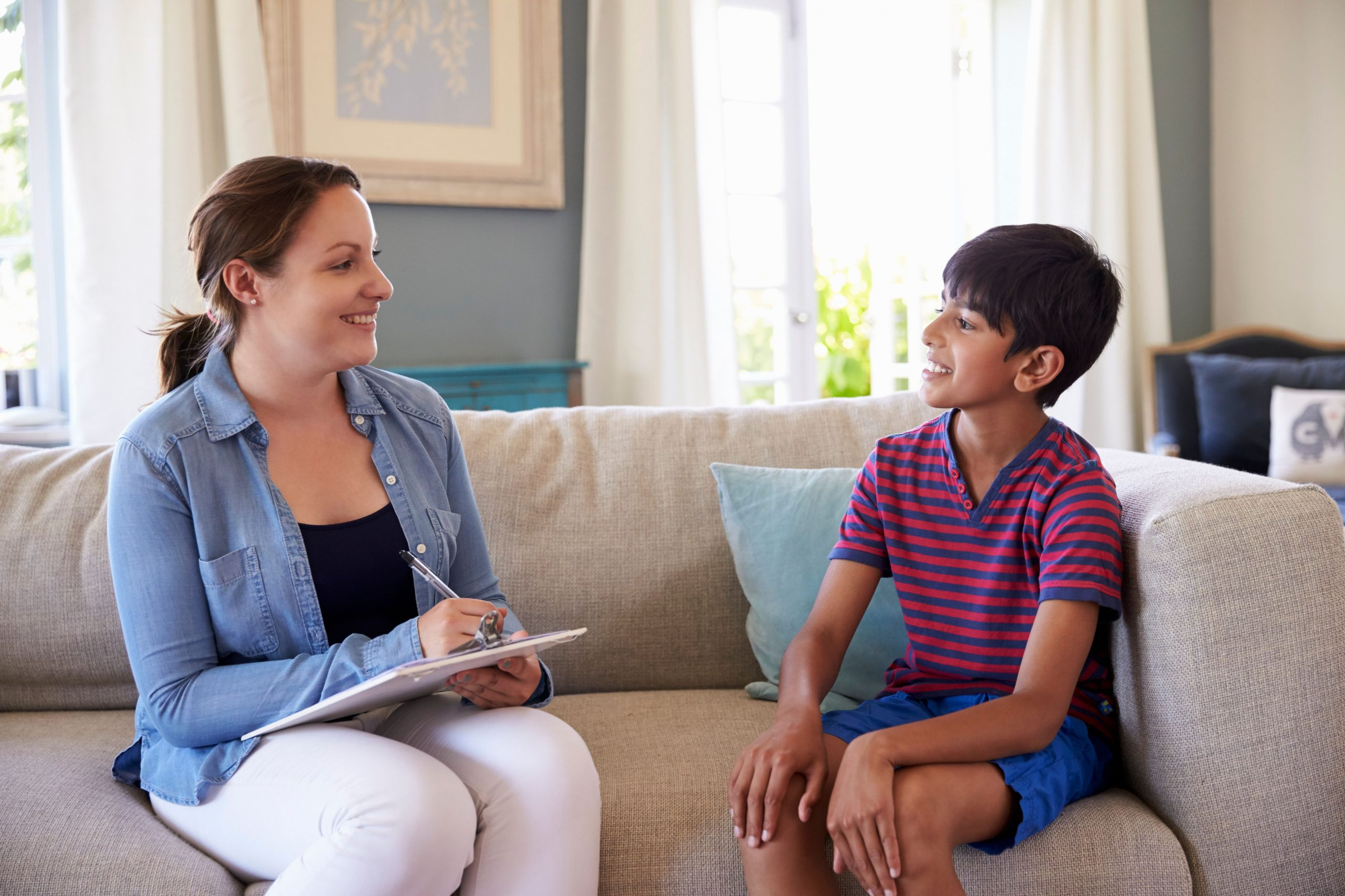 Woman with a clipboard talking to a young boy in a living room