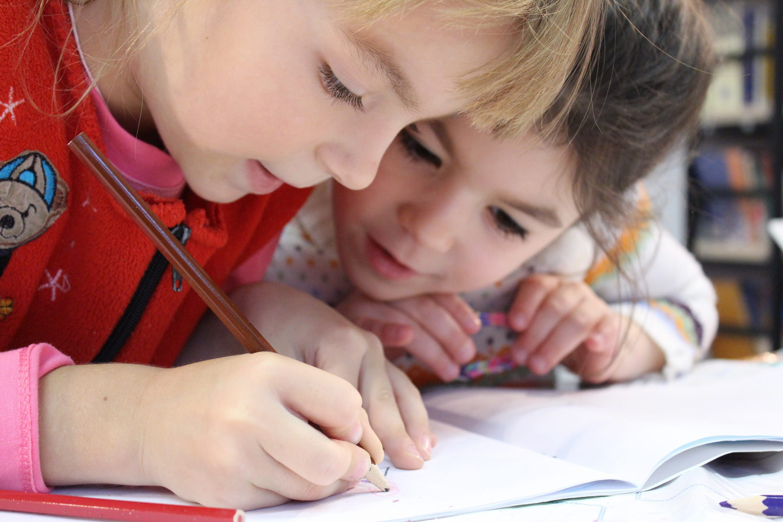 Two young children coloring together